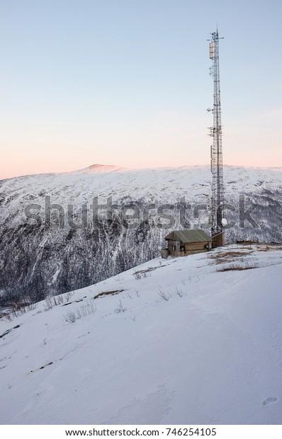Remote telecommunication mast on snowy mountain