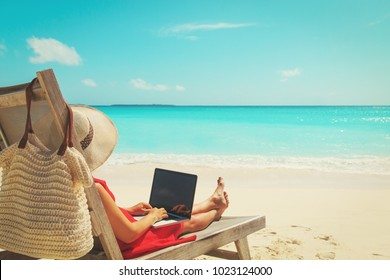 remote work concept -young woman with laptop on beach