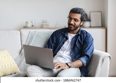 Remote Work. Handsome Eastern Freelancer Guy Working With Laptop At Home, Arab Millennial Man Sitting On Couch In Living Room And Using Computer, Enjoying Distance Job Opportunities, Copy Space
