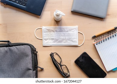 remote work kit on wooden office desk with hand sanitizer and face mask, a solution against the spread of corona virus for quarantined employees - Shutterstock ID 1672044127