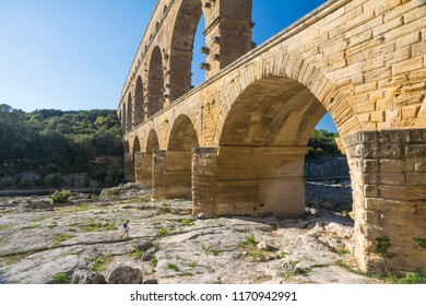 Remoulins , France - august 12, 2016:people swim and canoe near the Pont du Gard Roman aqueduct during a sunny day