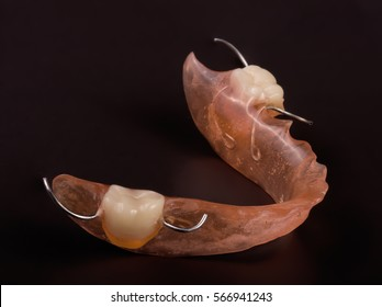 removable partial denture on a dark background