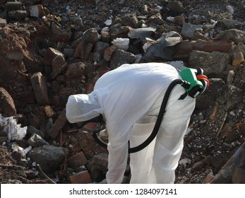Removal asbestos. Worker with special suit and mask on construction site.