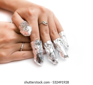 Removal of gel nail polish using a foil. Isolated on white.