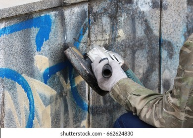 Removal of graffiti on a concrete wall of an underground passage with the help of a angle grinder