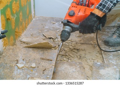 Removal of old floor during a renovation of housing from demolition hammer, fragments of ceramic tiles