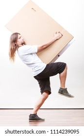 Removal service and delivery concept. Young male guy postal courier holding big very heavy cube package carton.