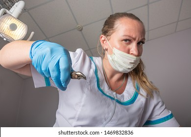 Removal of a tooth. Surgery, dentistry, bottom up view from patient to doctor. Doctor woman in a medical mask and with forceps in her hands removes a tooth, close-up.