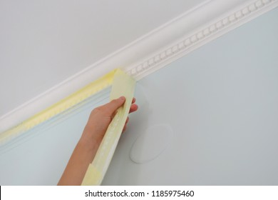 Remove paper masking tape from after painting. Removing masking tape from wall.