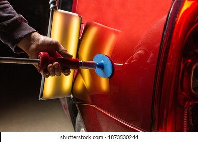 Removing dents on the car. PDR technology. Car body repair without painting.