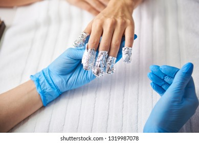 Removing gel nail polish. Top view close up picture of beautician hand in blue sterile gloves holding woman arm with foil
