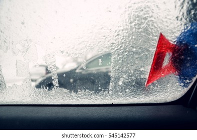 Removing ice from the car window with the red scraper