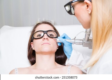 Removing mole from face of a young woman with medical laser.