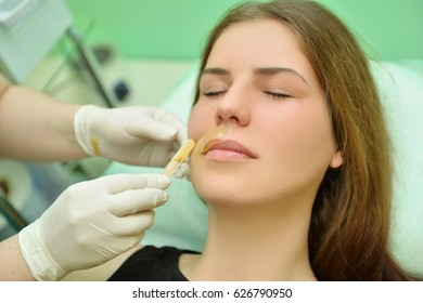 Removing the mustache of a woman with hot wax in a beauty salon