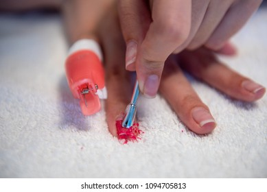 Removing nail polish with reusable plastic pinches and cotton pads soaked with acetone and nail spatula
