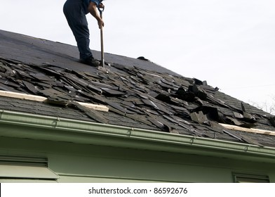 Removing old shingles to prepare a roof for a new installation