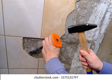 Removing old tiles from the wall in the kitchen using a chisel with a special plastic nozzle for safety when hammering. Do it yourself apartment repair. Construction garbage. Hand tool