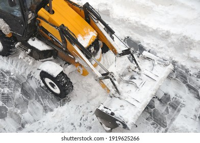 Removing snow accumulations using a tractor with attachments. Time of the year.