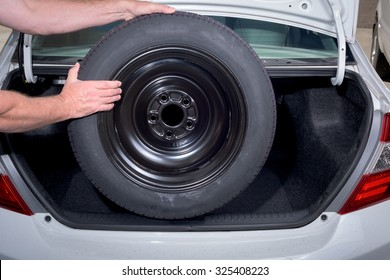 Removing a spare tire from the trunk of a car