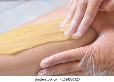 Removing unnecessary hair on the legs. Procedure sugaring in a beauty salon. Sugar depilation. Depilatory sugar paste