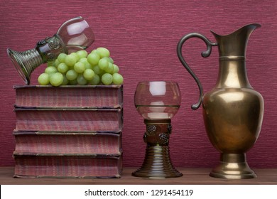 Renaissance, rummer wine glass, brass carafe, old books and grapes on the burgundy background.