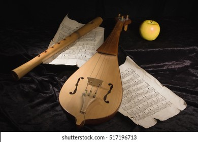 Renaissance violin (rebec) and alto recorder in a dark room with musical score