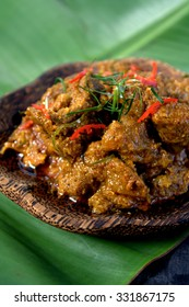 Rendang - spicy delicious meat dish cooked with herbs, spices and coconut milk served on black plate