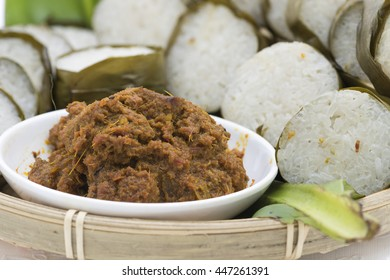 Rendang, a spicy meat dish cooked with ginger, galangal, turmeric, lemongrass, garlic, shallot, chili and other spices. A Malay cuisine. Background is slices of glutinous rice lined with banana leave.