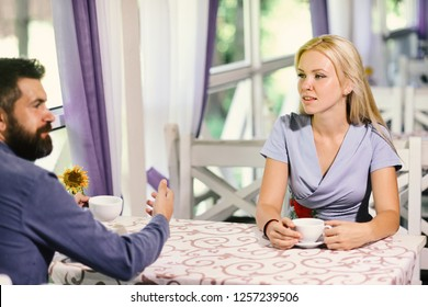 Rendezvous and coffee break concept. Girl with blond hair and bearded guy on light cafe background. Couple in love holds cups of coffee at table. Woman with busy face and man have a date.