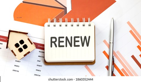 RENEW text on the notepad with paper sheet with pen and wooden house