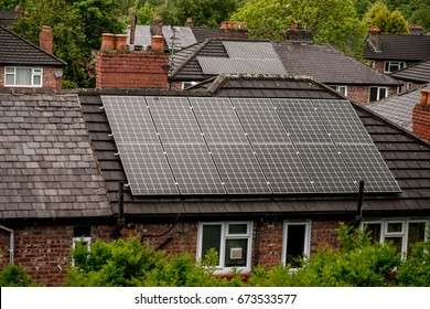 Renewable clean green energy saving efficient photovoltaic solar panels on multiple gable suburban house roof over blue sky Manchester UK