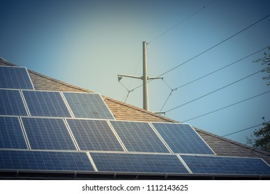 Renewable clean vs. traditional energy concept. Close-up solar panel system on asphalt shingles rooftop and power pylon wires. Rail-less racking battery storage at Grapevine, Texas, USA blue sky