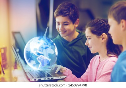 renewable energy, science and technology concept - group of happy children with laptop computer, earth planet hologram and wind turbine model at school