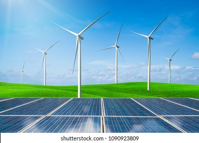 Renewable Energy - Solar panels and wind turbines on a green grass against blue sky.