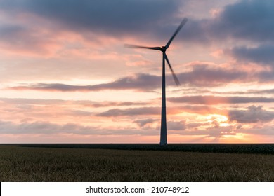 Renewable green energy coming from a windmill at sunset.