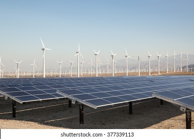 Renewable Solar Energy and Windmills Mountains in the background. Sunlight, solar panels and wind turbines. Environmental conservation and alternative power generation methods.