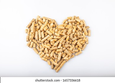 Renewable wood heating pellets shape heart as a gentle sign for the environment isolated on white background