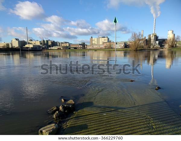 RENKUM, THE NETHERLANDS - JANUARY 2016: Paper plant along the riverside, high water level. Parenco paper mill is located along the Lower Rhine at Renkum.