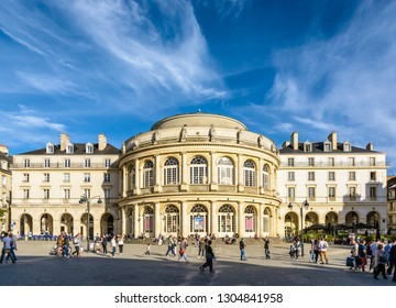 Rennes, France - October 13, 2018: Front view of the rounded facade of the opera house with people strolling on the pedestrian cobbled square by a sunny saturday afternoon under a deep blue sky.