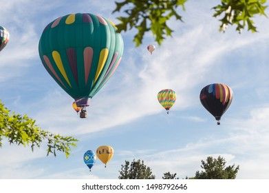 Reno, Nevada / USA - 09 07 2019: Colorful hot air balloons float over Reno, Nevada in at sunrise for the yearly Reno Hot Air Balloon Race.