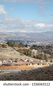 Reno, Nevada / USA - March 1 2019: Housing development under construction in a suburban valley, with downtown sprawl in the distance, with space for text on top and bottom