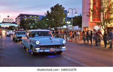 Reno, Nevada/USA - Aug 8,2019: Blue Vintage Car riding in a parade at Reno downtown in Hot August Nights Event with a famous Reno Arch in the back. People lining along the road to see the parade.