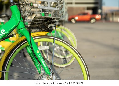 Reno, NV, USA 2018-10-27 - Closeup of Lime bikes ready to ride lined up in an open lot with cars parked in background.