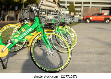 Reno, NV, USA 2018-10-27 - Lime bikes ready to ride lined up in an open lot with cars parked in background.