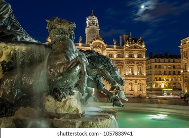 Renovated fountain Bartholdi and Hotel de Ville de Lyon at Place des Terreaux in the evening.