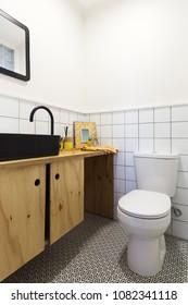 Renovated powder room with decorative floor tiles and black vani