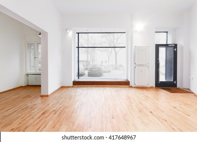 renovated room with shopping window - empty store / shop with wooden floor and white walls