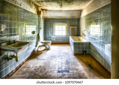 Renovated and very dirty bathroom with blue tiles in an old abandoned house