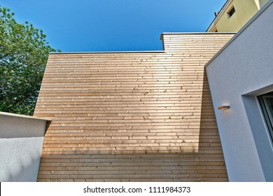 Renovated white ciment wall and insulating wood cladding in outdoor courtyard