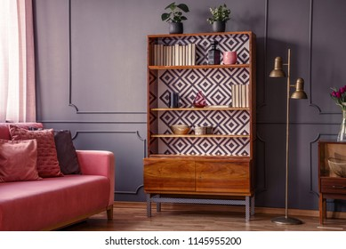 Renovated wooden bookcase with geometrical pattern and a brass floor lamp in a classy, dark living room interior with a comfortable pink settee